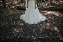 legs of a bride standing in the woods