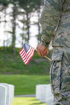 soldier holding an American flag standing in a cemetery