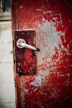 door handle on an old red door