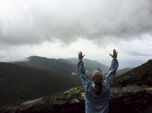 hands raised on a mountain top