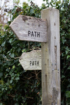 Wooden trail markers denoting the direction of the path, covered with moss and lichens