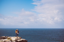 couple standing on the edge of a cliff near the sea