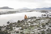 a woman in a coat walking along a muddy shore in Alaska