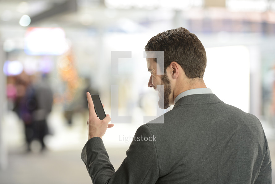 Young businessman on the cell phone inside an airport with blury background