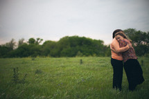 Mother and daughter embracing in a field.