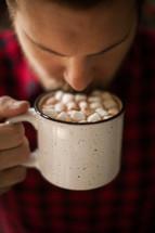 a man drinking a mug of hot chocolate
