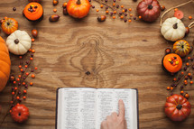 finger pointing to Bible scripture surrounded by fall themed decorations