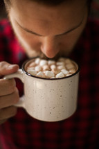a man drinking hot cocoa