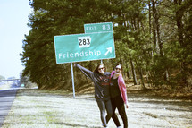 friends in front of a friendship street sign