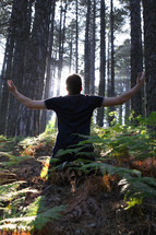 man standing in a forest with his hands raised in worship to God