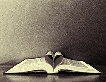 a Bible with pages forming a heart