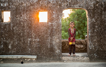 young boy standing in a doorway