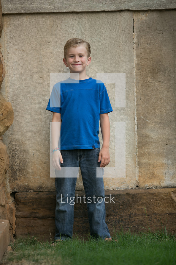 smiling little boy in front of a concrete wall