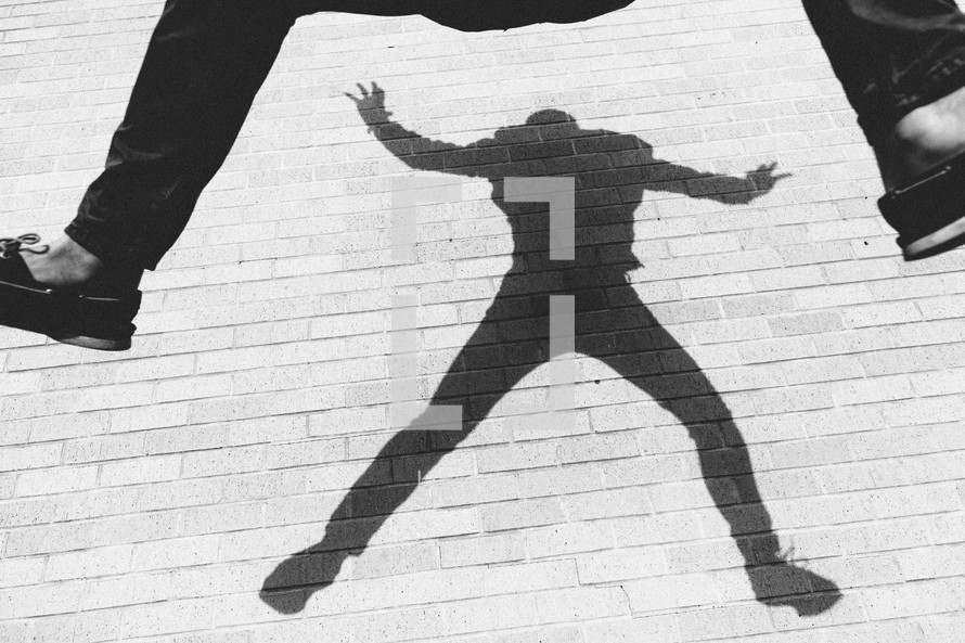 A young adult jumping up in the air - His shadow appearing on a brick wall