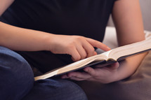 girl reading a Bible on a couch