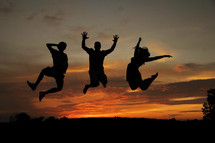 A silhouette of three people jumping into the air.