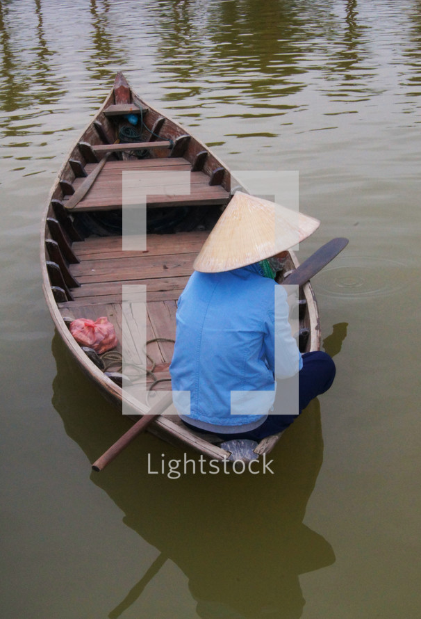 A Vietnamese lady sitting on a wooden boat