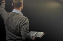 a preacher holding  a Bible during his sermon
