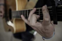 Man's finger playing guitar