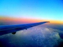 Airplane wing over clouds