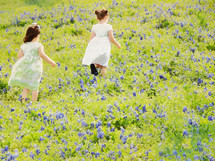 girls running in a field of bluebonnets