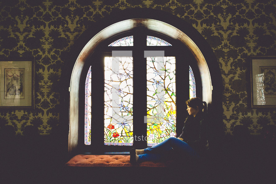 A woman sitting in a window thinking.