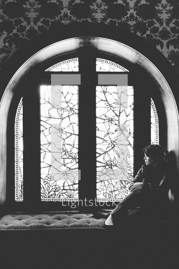 woman sitting in a window