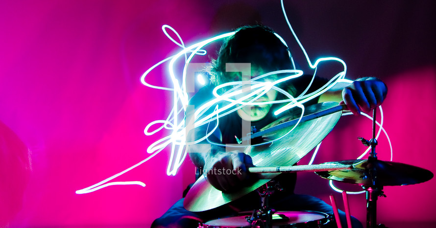 swirling lights around a drummer in a band on stage at a concert