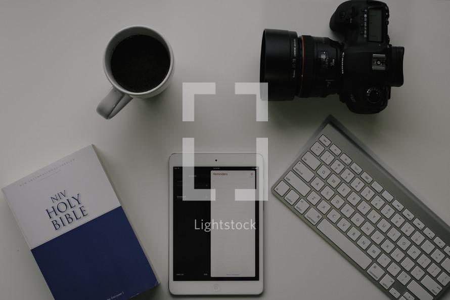 NIV Holy Bible, tablet, keyboard, camera, coffee mug