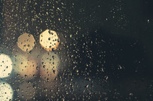 rain drops on a window and bokeh lights at night