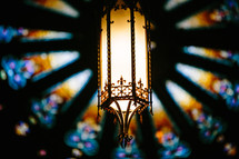 hanging lantern in a church and stained glass window