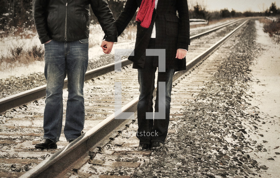 Couple holding hands as they walk along a railroad track.