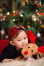 toddler girl on a fur rug with a stuffed animal reindeer under a Christmas tree