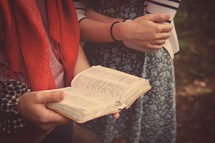reading a Bible together outdoors