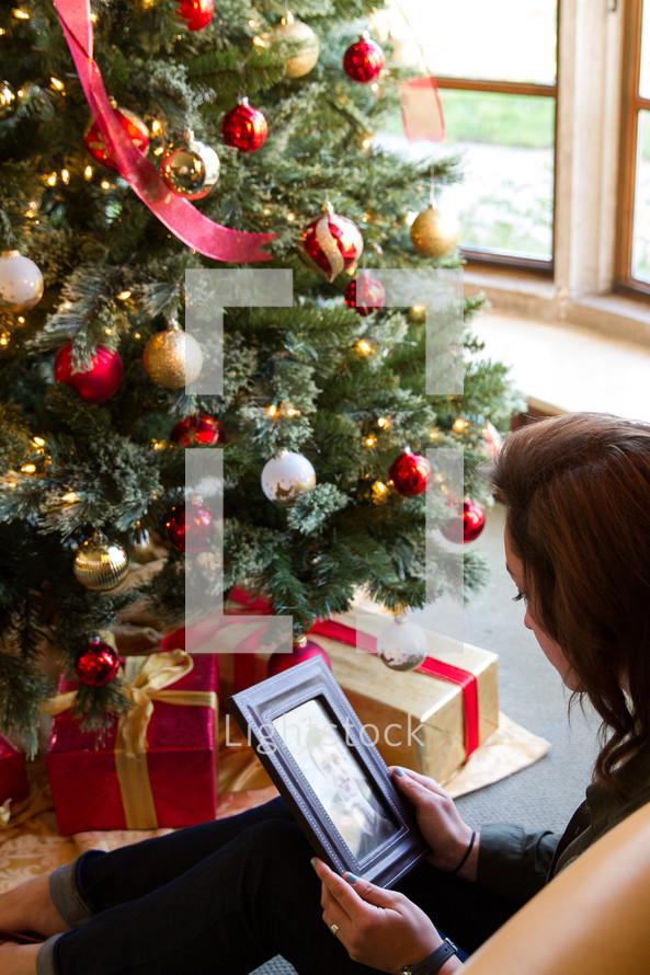 sad young woman sitting near a Christmas tree