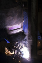 sparks from a welder wearing a mask