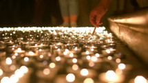 lighting prayer candles in a church