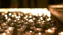 lighting prayer candles in a church at night