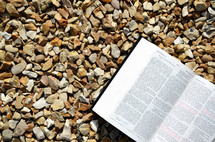 open Bible on gravel