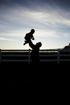 silhouette of a father holding up his son