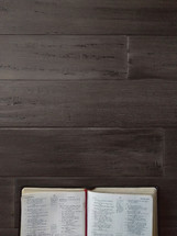 An open Bible on a dark wood table with space for text.