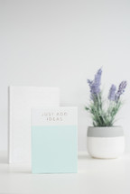 potted lavender plant, book, and journal on a white desk