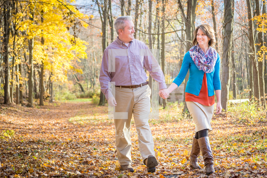 couple walking holding hands in a fall forest