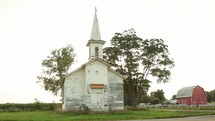a rural white church and red barn