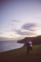 couple hugging and looking out at a coastline