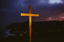 Wooden cross on a hill over a city at nightfall.