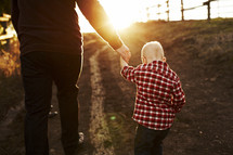 father and son walking holding hands