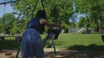 a mother pushing a baby on a swing