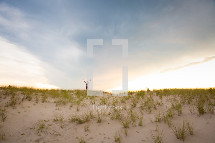 Man worshiping with raised outstretched arms looking out at sky on top of sandy grassy hill