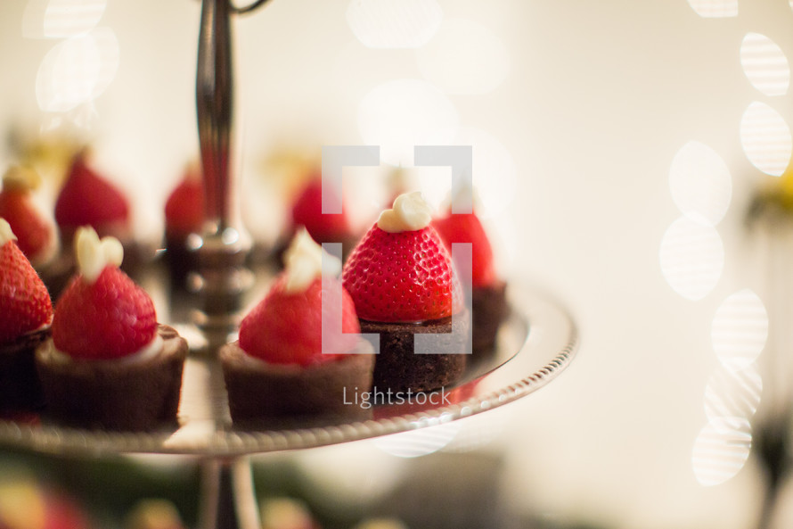 strawberries and icing in the shape of Santa hats on brownies on a platter